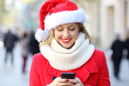 Front view of a happy woman sending phone text on christmas in the street Stock Photo