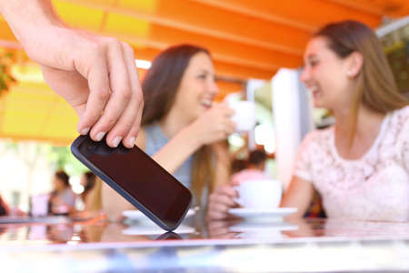 Distracted friends talking in a bar and close up of a thief hand stealing phone on foreground