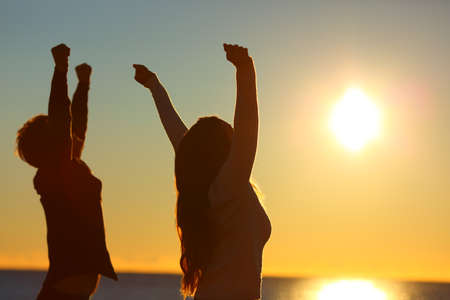 Silhouette of two excited friends raising arms at sunset on the beach with the sun in the background