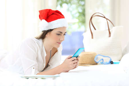 Woman using a smart phone on christmas holidays lying on a bed in an hotel room