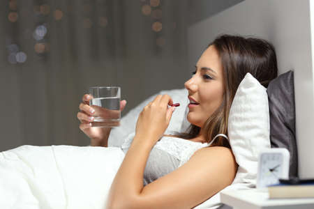 Profile of a happy girl taking a pill before sleep on a bed in the night at home Stock Photo