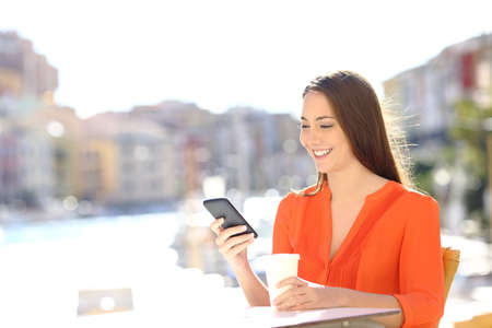 Happy lady uses a smart phone in a coffee shop of a coast town on vacation