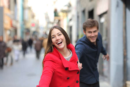 Happy couple running together towards camera in the street in winter