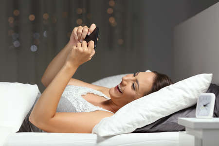 Happy girl watching video or playing games on a smartphone lying on a bed in the night at home