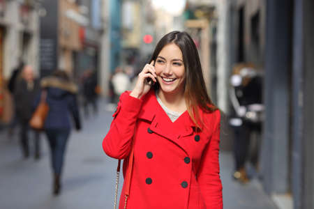 Front view of a happy woman in red walking talking on phone in winter
