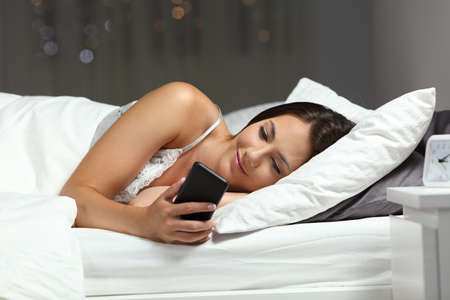 Relaxed woman using a smart phone in the night lying on a bed at home