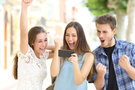 Excited friends watching media content from smartphone in the street