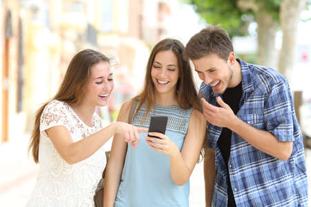 Three happy friends watching smartphone content in the street