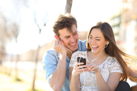Joyful couple listening to music from a smartphone sitting on a bench in a pak Stockfoto