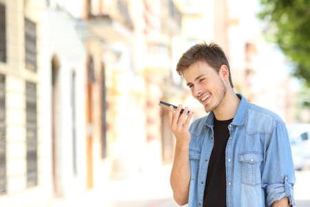 Niño feliz con reconocimiento de voz en un teléfono inteligente en la calle