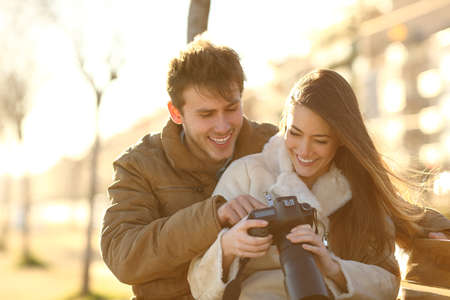 Happy couple checking photos on a dslr camera sitting on a bench in a park