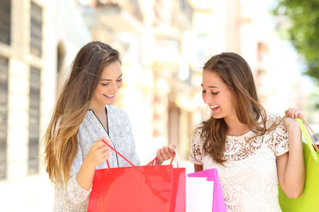 Two happy shoppers looking at shopping bags content in the street