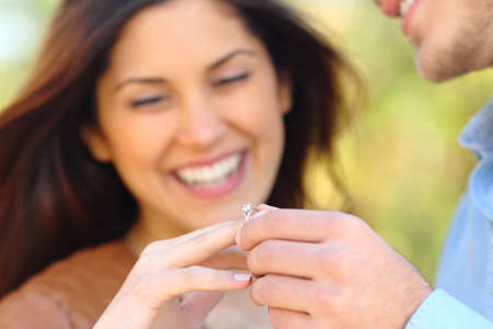 Happy man putting engagement ring to his glad girlfriend after proposal outdoors in a park Stok Fotoğraf