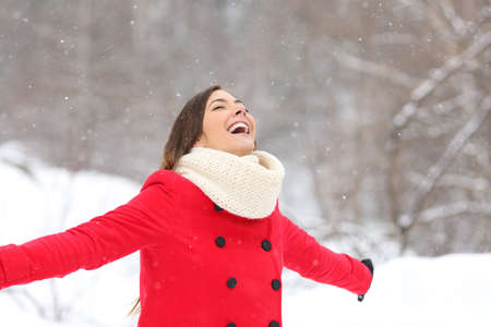 Joyful woman breathing fresh air enjoying snow in a snowy mountain Stock Photo
