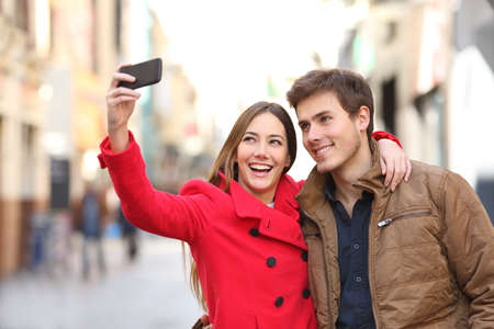 Happy couple taking selfies with a smart phone in the street in winter