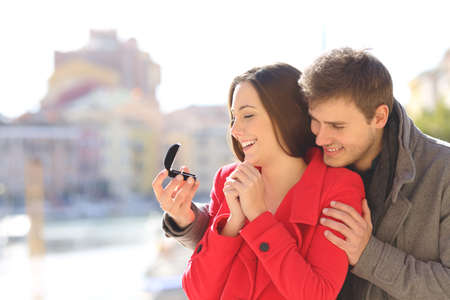 Man proposing marriage to his happy girlfriend in a coast town during winter holiday Stock Photo