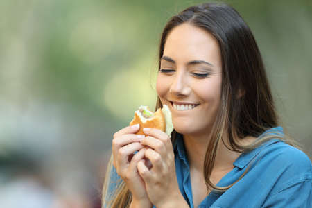 Happy woman eating and looking a delicious burger in the street