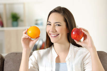 Happy girl showing apple and orange fruits sitting on a couch in the living room at home Foto de archivo - 112007913