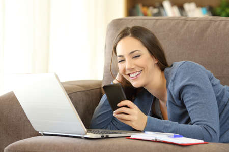 Happy woman using a phone and laptop lying on a couch in the living room at home