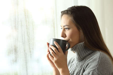 Happy woman drinking coffee looking at rain through a window at home or hotel in winter