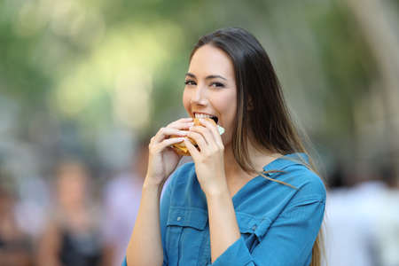 Happy woman biting a burger looking at camera in the street