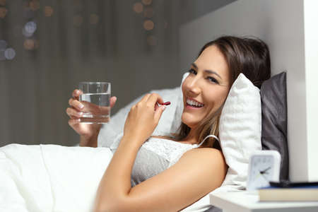 Happy woman taking a pill holding a glass of water in the night looking at you Stock Photo