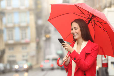 Happy woman in red using a smart phone under the rain in winter in the street