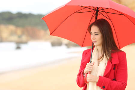 Serious woman in red contemplating the beach in winter under an umbrella Stok Fotoğraf