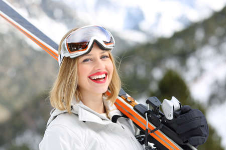 Happy skier looking at camera holding skis in the mountain in winter holiday 写真素材