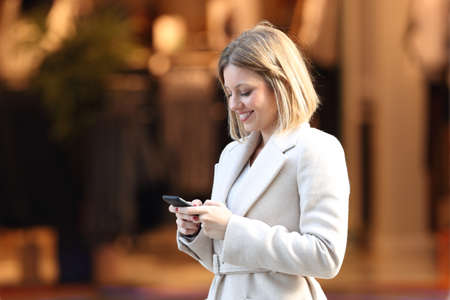 Lady uses a smart phone in the street of a commercial centre Stock Photo