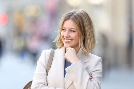 Happy beauty woman looking at side in the street in winter Stock Photo