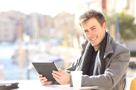 Happy self employed holding a tablet looking at you sitting in a coffee shop terrace of a coast town Banque d'images - 112243018