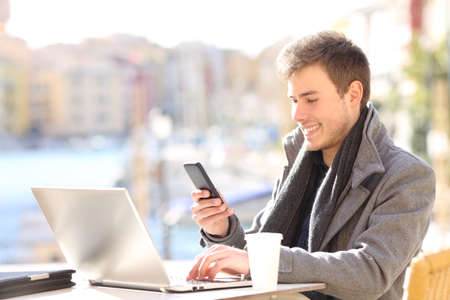 Happy entrepreneur using smart phone and laptop in a bar terrace of a coast town