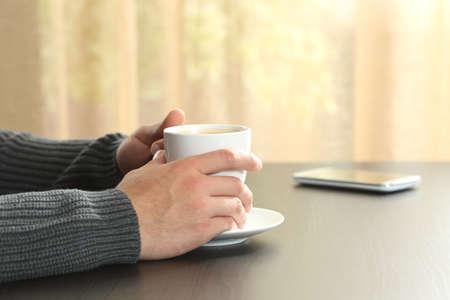 Cerca de las manos de un hombre sosteniendo una taza de café sobre una mesa Foto de archivo
