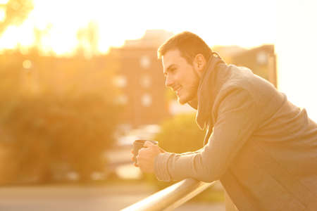 Side view portrait of a happy man drinking coffee looking away from a balcony in winter at sunset Stock Photo
