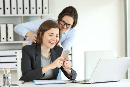 Furious office worker angry with her lazy colleague trying to strangle Stock Photo