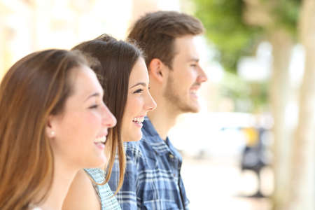 Profile of three happy friends looking away in the street