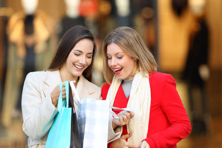Front view of two happy shoppers checking purchases in a shooping bag in a commercial centre