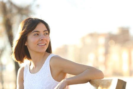 Porträt einer glücklichen Frau, die auf einer Bank in einem Park sitzt