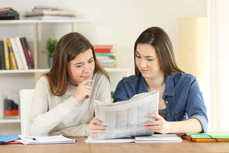 Front view portrait of two students finding suspicious news in a newspaper at home Stock Photo
