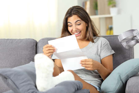 Excited disabled girl reading good news in a paper letter sitting on a couch at home