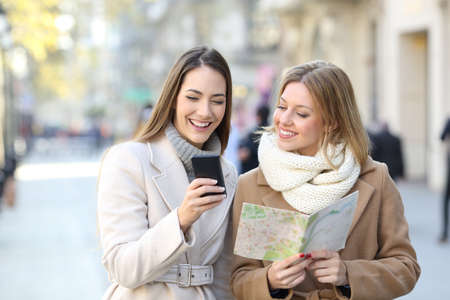 Front view of two happy tourists comparing smart phone contant and paper map in winter holiday in the street Zdjęcie Seryjne