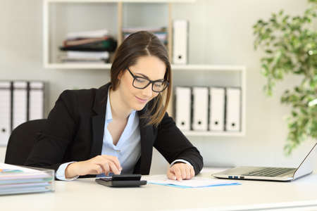 Office worker wearing eyeglasses doing accounting on a desk Imagens - 112439764