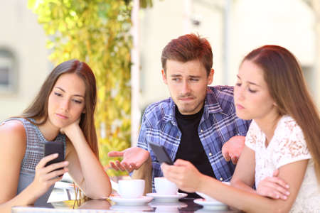 Man being ignored by his friends who are using their smart phones