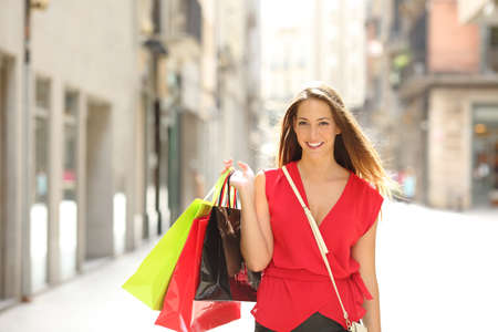Front view portrait of a happy shopper walking towards camera holding shopping bags looking at you Stock Photo