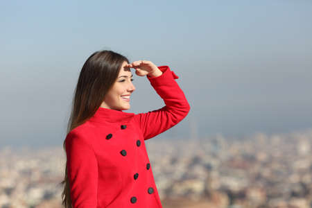 Happy woman in red scouting with hand on forehead in winter with urban background Stock Photo