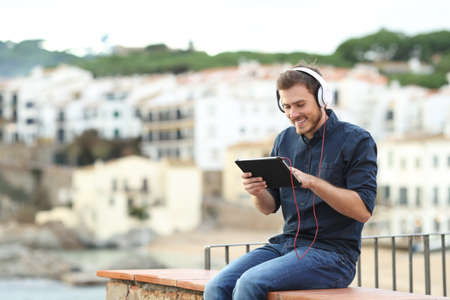 Happy man watching media on a tablet on a ledge with a town in the background Stock Photo