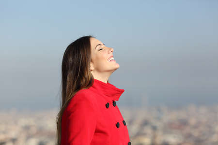 Side view portrait of a happy woman breathing fresh air with urban background in winter