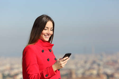 Happy wearing red jacket in winter using smart phone outdoors Stock Photo
