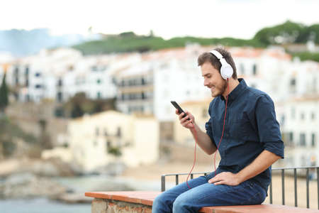 Happy man wearing headphones listening to music on a ledge with a town in the background Stock Photo